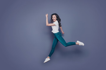 Slim funky attractive adorable pretty stylish trendy nice graceful cheerful curly-haired brunette girl in casual white t-shirt and jeans, running rush hour in air, isolated on grey background