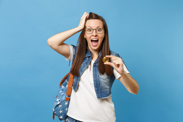 Young amazed shocked woman student with opened mouth clinging to head hold bitcoin metal coin of golden color isolated on blue background. Future currency. Education in high school university college.