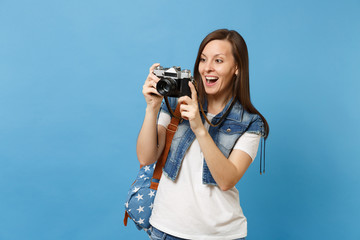 Portrait of young excited woman student with opened mouth with backpack take pictures on retro vintage photo camera isolated on blue background. Education in university. Copy space for advertisement.