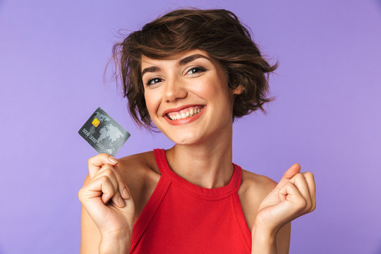 Smiling Pretty brunette woman holding credit card while rejoices