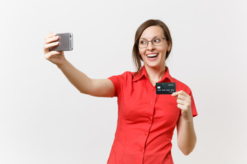 Excited business woman in red shirt doing taking selfie shot on mobile phone with credit bank card, cashless money isolated on white background. Education teaching in high school university concept.