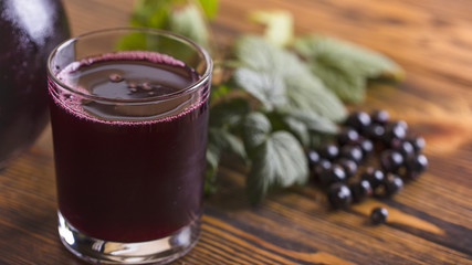 Fresh blackcurrant juice with some fruits on wooden background