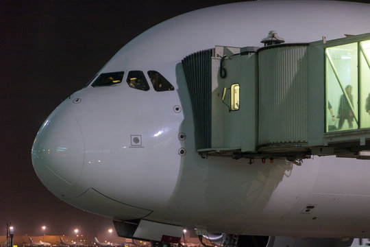 Passengers depart from the aircraft. The plane is standing by the tunnel at the night airport.
