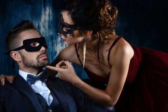 Sexy woman female in black carnaval mask red expensive dress and gold earnings seduces millionaire man male in suit, bow tie and black carnaval mask. Sex, tempts, harassment, sexism, seduction issues