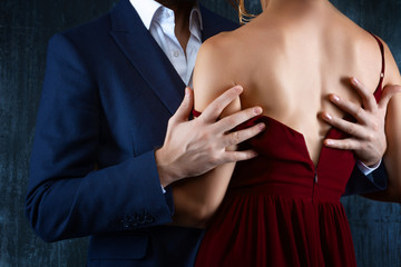 Elegant couple in love. Rich tidy neat man male hugs luxury woman female in red evening dress with expensive gold earrings. Romantic dating body part, sex social issues, relationship concept