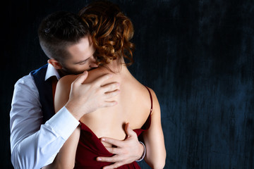 Elegant couple in love. Rich tidy neat man male kissing in shoulder of luxury woman female in red evening dress with expensive gold earrings. Romantic dating body part, sex issue, relationship concept