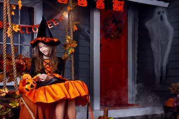 Funny girl child kid in halloween witch costume with black hat and orange pumpkins basket with spooky face for candies and sweets sitting on swing ready for celebration autumn holiday halloween. Wall mural