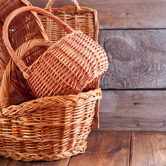 Woven empty baskets from natural handmade vines for mushrooms, handicrafts, storage, walks, picnic on a wooden table, copy space