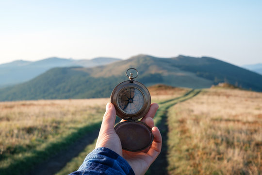 Man with compass in hand on mountains road. Travel concept. Landscape photography