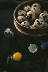 Fresh organic quail eggs in a vintage sieve on an old grunge metal background. Dark and moody picture. Low key. Close up, selective focus. Toned image