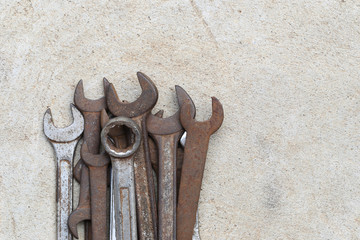 Old wrench tool with rust placed on the concrete floor background.