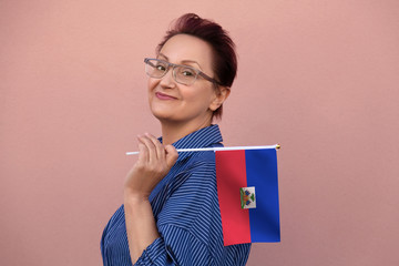 Haiti flag. Woman holding  Haiti flag. Nice portrait of middle aged lady 40 50 years old with a national flag over pink wall background outdoors.