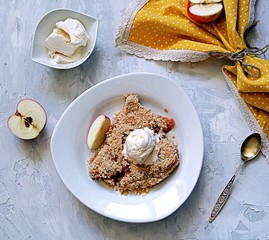 Apple crumble pie with whole-grain flour, oat flakes and cinnamon. Served warm with a vanilla ice cream ball.