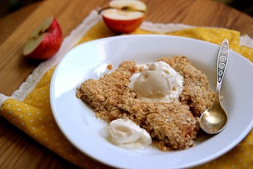 Apple crumble pie with whole-grain flour, oat flakes and cinnamon. Served warm with a vanilla ice cream ball..