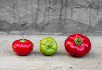 Red and green peppers on grey concrete background