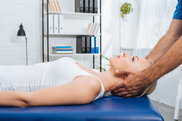 partial view of physiotherapist massaging neck of patient that lying on massage table in clinic