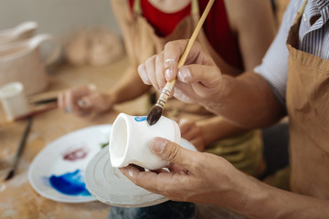 Painting brush. Male potter holding painting brush while decorating clay pot finishing his work day