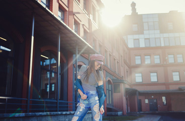Fashion woman with long hair smiling in urban background. Girl wearing casual clothes.