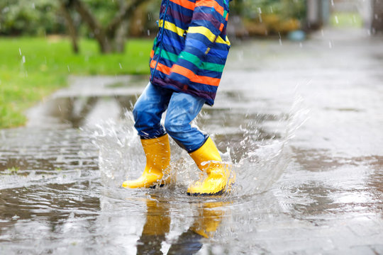 Close-up of kid wearing yellow rain boots and walking during sleet, rain and snow on cold day. Child in colorful fashion casual clothes jumping in a puddle. Having fun outdoors
