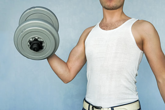 an aspiring athlete trains your biceps. beginning sportsman. guy raising a dumbbell. Home exercises for weight gain