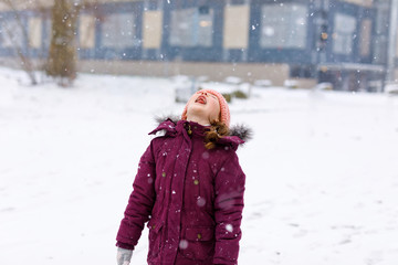 Adorable little kid girl in colorful clothes playing outdoors during snowfall. Active leisure with children in winter on cold snowy days. Happy child on winter street in the city: