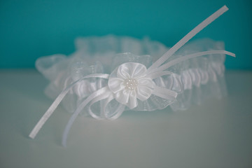 Silky white garter with flower detail and white pearly beads, isolated tasteful accessory, customary worn on the upper thigh by bride on her wedding day positioned against white and blue background