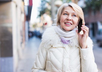 Smiling mature woman talking on phone and walking