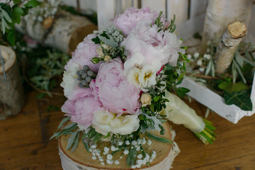 Pale pink colored peonies, freesias and greenery bouquet sitting on top of a rustic wooden table, floral arrangement for the bride, perfect accessory for wedding ceremony