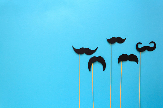 Paper mustache on booth props on blue paper background. Cut out style. Movember concept. Top view. Flat lay. Copy space