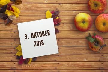 """Herbstlaub, Äpfel und Karton mit Aufschrift """"3. Oktober 2018"""""""