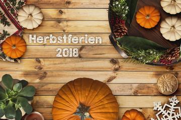 """Holzhintergrund mit Aufschrift """"Herbstferien 2018"""" mit herbstlicher Dekoration"""
