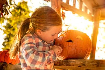 Little girl carving Halloween pumpkin outdoors.