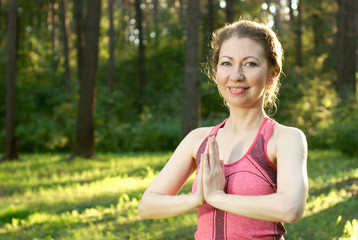 Beautiful young female make a yoga training in a sunny summer forest. Women's health concept photo.