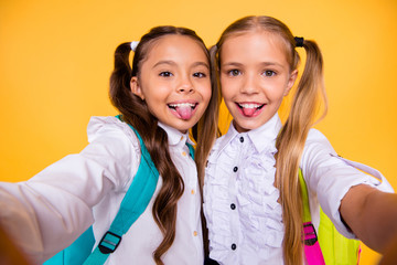 Close up portrait of cute, nice, lovely, sweet, adorable small girls take selfie on a smartphone isolated on yellow background look at the camera and show the tongue out