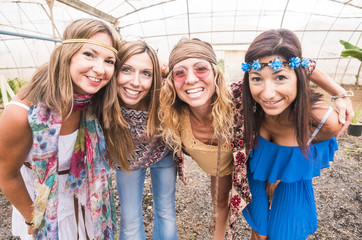 four young and beautiful cheerful females in a selfie portrait together hugging in friendship. colorful dress and clothes in hippy and freedom alternative style. smiles and joyful concept people