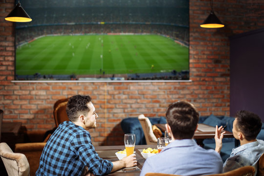 Happy friends having leisure in pub watching sport in TV together drinking beer