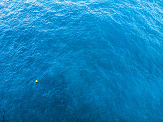 one buoy and sea marker in clear, azure, deep green and dark blue Mediterranean sea. Seacolor mixing consept. Backgournd pattern of sea and ocean marine colours. Aerial photo from drone.
