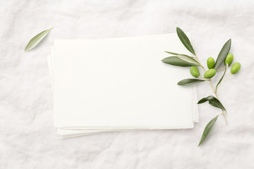 feminine minimalist styled wedding stationery  mockup with a stack of blank invitation cards and a fresh olive twig on a white soft linen background, flat lay / top view