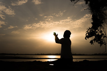 Silhouette Young asian muslim man praying on sunset,Ramadan festival concept