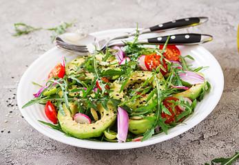 Diet menu. Healthy salad of fresh vegetables - tomatoes, avocado, arugula, radish and seeds on a bowl. Vegan food.