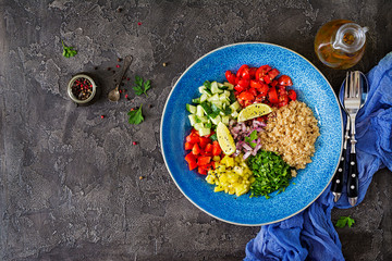 Salad with quinoa, arugula, sweet peppers, tomatoes and cucumber in bowl on a dark background. Healthy food, diet, detox and vegetarian concept. Buddha bowl. Top view. Flat lay