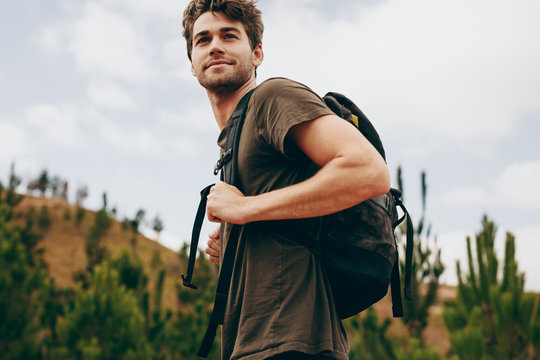 Man walking through a forest wearing a backpack.