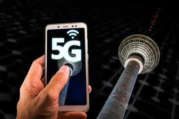 Smartphone with 5G on screen and Famous Berlin television tower or Fernsehturm on the background