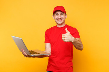 Delivery man isolated on yellow orange background. Professional male employee courier in red cap, t-shirt holding working typing on laptop pc computer. Service concept. Copy space for advertisement.