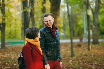 Young romantic couple in love cheerful woman, man in casual warm clothes walking by hands looking at each other in autumn city park outdoors in sunny day. Love relationship family lifestyle concept.