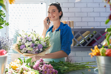 Obraz Young smiling florist holding flowers and connecting on mobile phone near workplace - fototapety do salonu