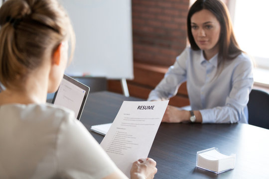 Back close up view of female employer holding applicant resume during office interview, millennial work candidate recruiting for open position, hr team hiring woman applying for job. Employment