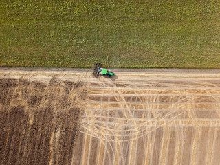 Wall Mural - Panoramic view of tractor plowing the soil after harvesting on the field. Top view from drone.