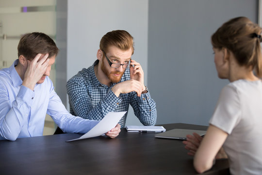 Concerned male recruiters reading applicant resume, unsure about her candidature for open position, doubtful serious hr managers considering woman candidate at hiring. Bad interview concept