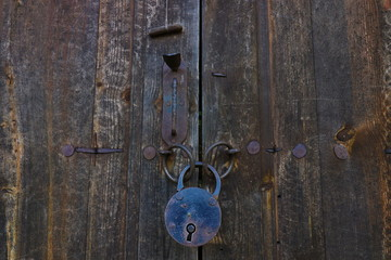 Old rusty opened lock without key. Vintage wooden door, close up concept photo. Security, metal.